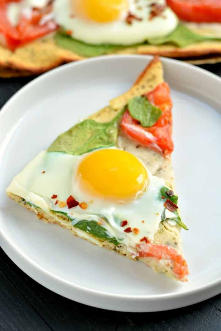 Wake up to Paleo Breakfast Pizza! Made with a simple coconut egg crust and topped with fresh veggies and cracked eggs, this is a perfect, easy meal for any time of day!
