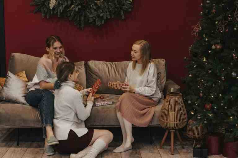 women in living room holding gifts