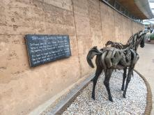 Driftwood horses infront of Rammed Earth walls