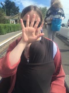 Tas hiding behind her hand