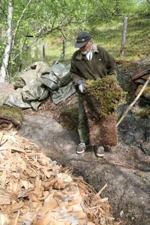 Sverre legger på den første rullen med torv. Foto: Roald Renmælmo