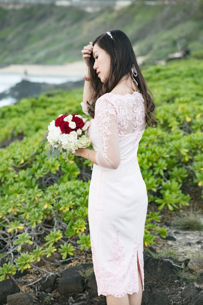 bride with flower bouquet taking photos at Hawaii beach