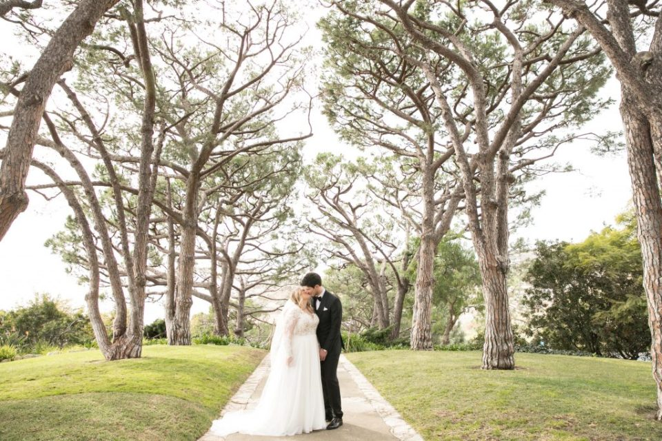 bride and groom kiss under tree lines path
