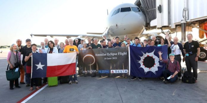 a group of people stand next to a plane, holding a sign advertising the sky & telescope eclipse tour