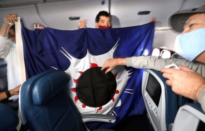 three people hold up a blue flat with an image of a eclipse with a white flare in the inside of an airplane