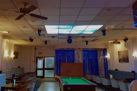 Dark room with snooker table lightened with large sky ceiling panels
