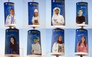 Absolwenci uniwersytetu - plakaty na latarniach w Doha.