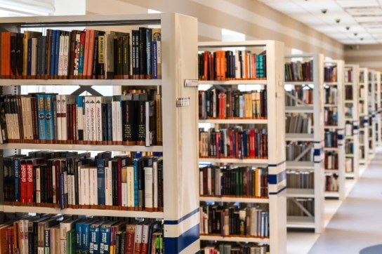 "An image of books on shelves in a library. The image is used on a home automation roundup under the heading, ""For those who want to learn more."""