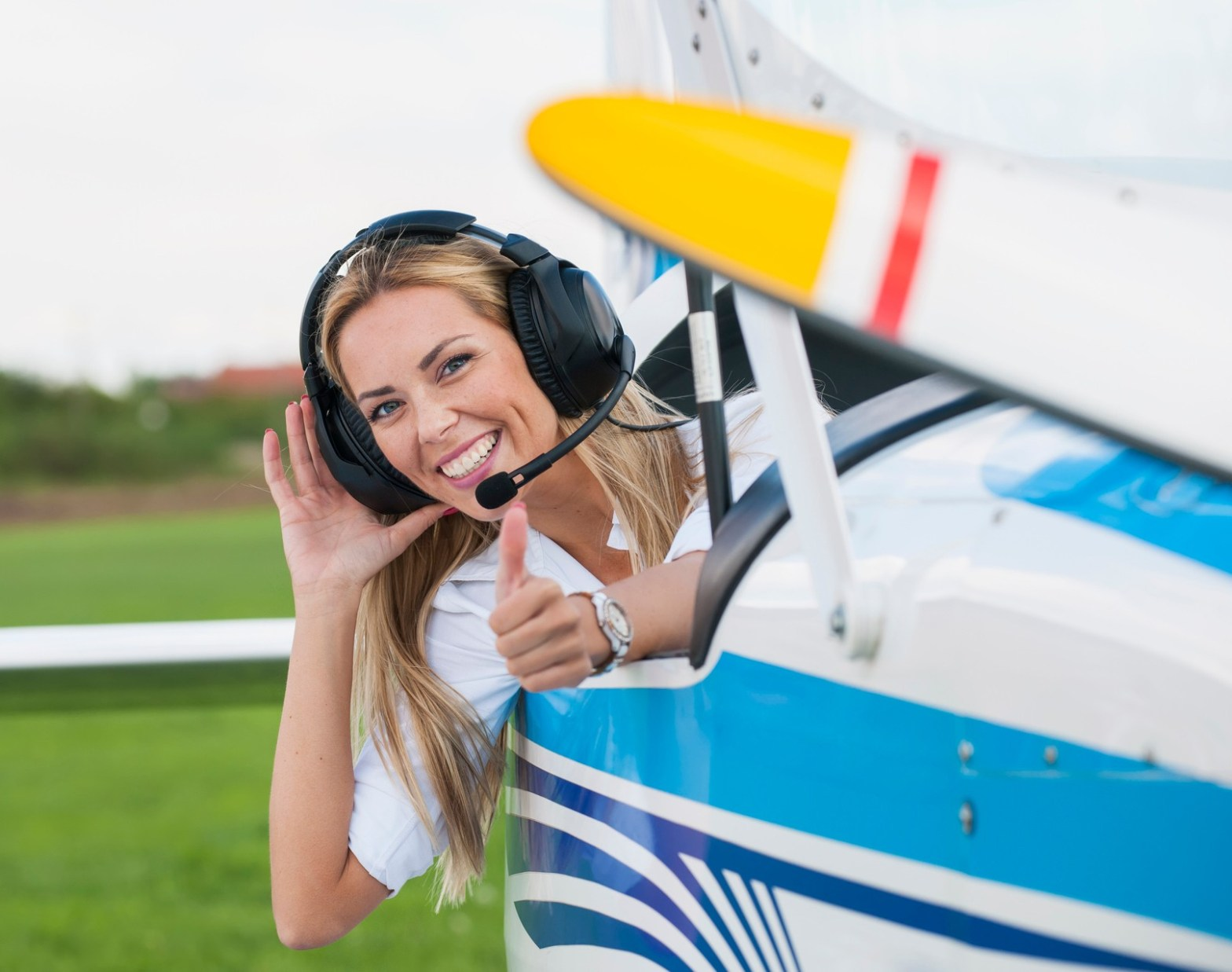 Woman pilot looking at camera, preparing for flying, Sky Review