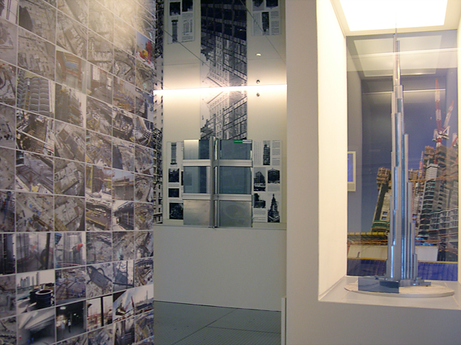 Gallery view of the presentation model case and wall with a grid of construction photographs