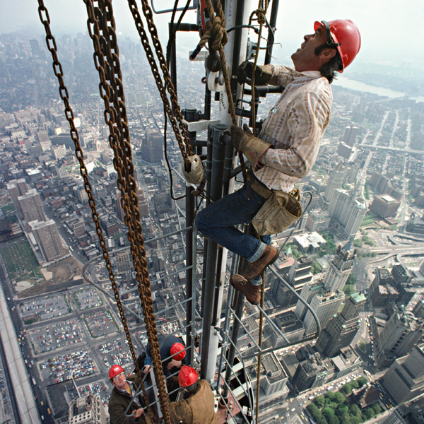 Photograph of construction workers climbing the antenna of the North Tower of the World Trade Center. Photograph by Peter B. Kaplan