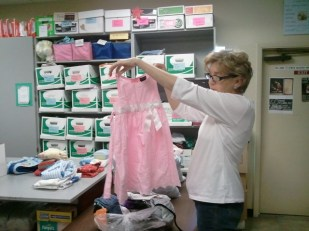 Denise is having fun sorting through all the frilly frocks and thinking of the happy little girls who will wear them.