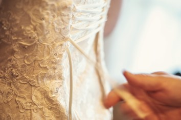 The Bride is getting ready - close up of dress tying