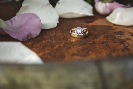 Ring photo taken by skys the limit production on top of a wine barrel with purple and white flower petals around.