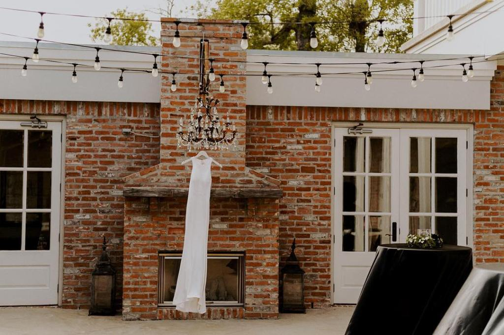 Wedding dress hanging from chandelier beside a brick venue in Beaumont, Texas in daylight.