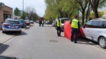 Policjanci pracują na miejscu zdarzenia - postrzelenia policjanta. Zdjęcie przedstawia jezdnię, po boku zaparkowane samochody, także radiowozy, czerwony parawan oraz poruszających się na miejscu policjantów.