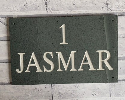 an oblong piece of green westmorland slate engraved with a house name and number then painted and finished with a matt sealer. drill holes in each corner to facilitate fixing to a wall or gate