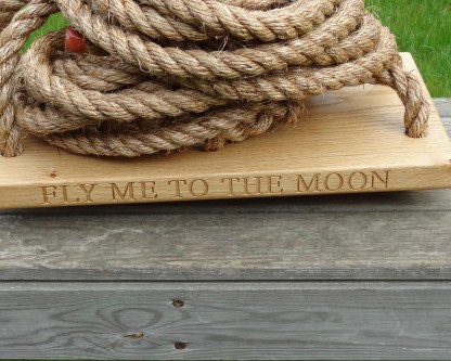 solid oak traditional garden swing with fly me to the moon engraved along the edge of the swing seat