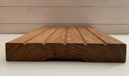 solid oak bread board grooves on the underside to facilitate lifting. open ended grooves on the surface to catch crumbs and facilitate sweeping away