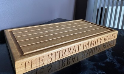 solid oak carving board with a channel around the surface edge and grooves along the top to catch meat juices, personalised inscription engraved on the front edge