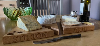 three solid oak cheese boards in the shape of a wedge with various holes along the edges and the surface designed to look like a piece of cheese. engraved with stilton and brie along the front edge