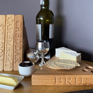 slate and oak solid oak cheese board in the shape of a wedge with various holes along the edges and the surface designed to look like a piece of cheese. engraved with brie along the front edge, personalised oak gifts