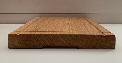 surface of a solid oak chopping board with 4 grooves across the top and grooves on the underside to facilitate lifting