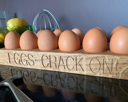 12 egg rack in solid oak engraved with eggs crack on along the front edge. handcrafted in solid oak, slate and oak personalised oak gifts