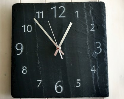 square welsh grey slate clock, with visible surface graining, engraved with a full face of bold numbers