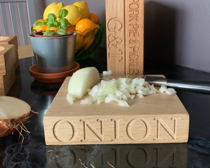 small solid oak chopping block engraved with onion along the front edge and garlic along the back edge