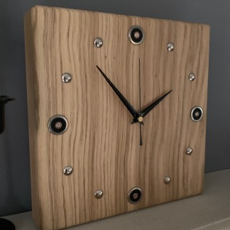 thick square solid oak block with a clock face made from chrome tacks and chrome/black cartridge caps