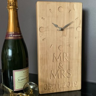 tall thin solid oak clock engraved with a contemporary style face and mr & mrs and a date in the bottom half