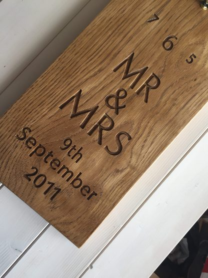 long thin solid oak wall clock with a full face of numbers and a personalised inscription engraved in the bottom half of the oak
