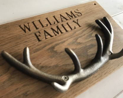 solid oak plaque engraved with a family name and fitted with cast iron stag antlers designed for use as coat or key hooks