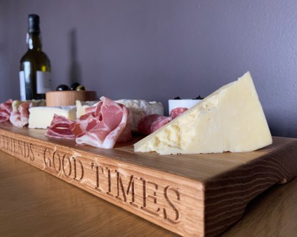 long thin solid oak serving board engraved along the front edge with good food, good friends, good times
