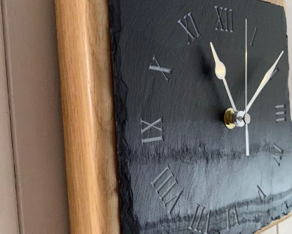 close up view of a square piece of welsh grey slate engraved with a roman numerals style clock face mounted on a thick oak block for wall mounting or freestanding