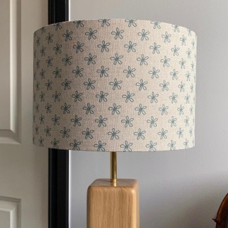 30cm drum lampshade in natural linen with a teal daisy print design, fitted on a solid oak lamp base