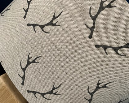 close up view of charcoal coloured stag antlers on natural linen fabric