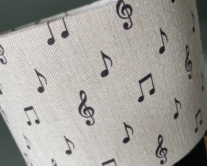 close up of a drum lampshade made using natural linen fabric digitally printed with dark charcoal coloured musical notes