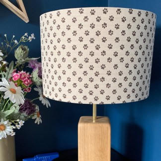 natural linen fabric printed with a chocolate coloured paw print made into a drum style lampshade