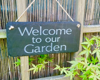 hand cut welsh grey slate engraved with three lines of text welcome to our garden, finished with natural jute rope for hanging