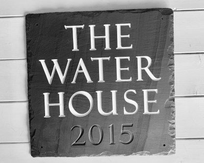full view of a hand cut welsh grey slate house sign engraved with four lines of text