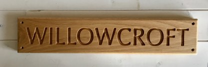 long thin solid oak house sign with a single line of text and drill holes in each corner for fixing