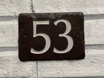 a slate house number in welsh heather slate engraved with the numbers 53 and painted in off white and finished with a matt sealer