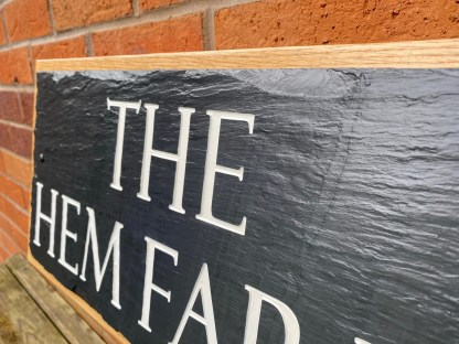 long view of an engraved slate house sign mounted on a solid oak back board designed to be fixed to a wall or post.