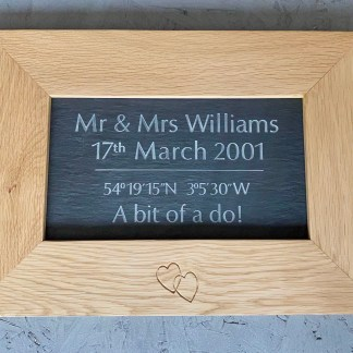 solid oak frame with engraved slate inset. engraving on the slate are the wedding details and show the name, date, venue gps coordinates and caption