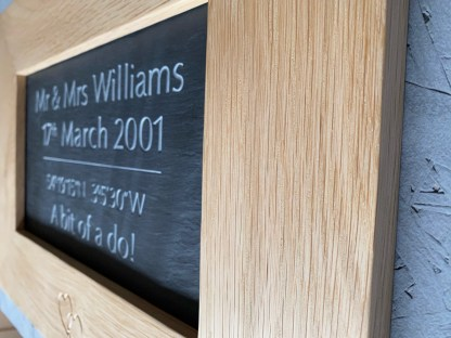 profile view of an oak frame with an engraved slate inside. The engraving is the wedding details, and shows the name, the date, the venue gps coordinates and the caption that described the wedding party