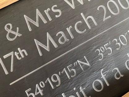 close up shot of engraved slate inside a solid oak frame