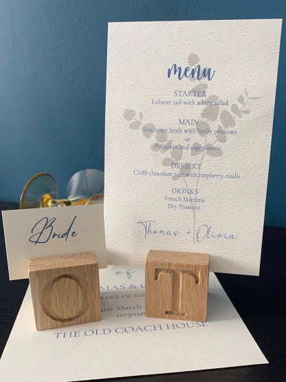 solid oak place card holder with engraved letter on the front and a menu card and name card set into the channel on the top
