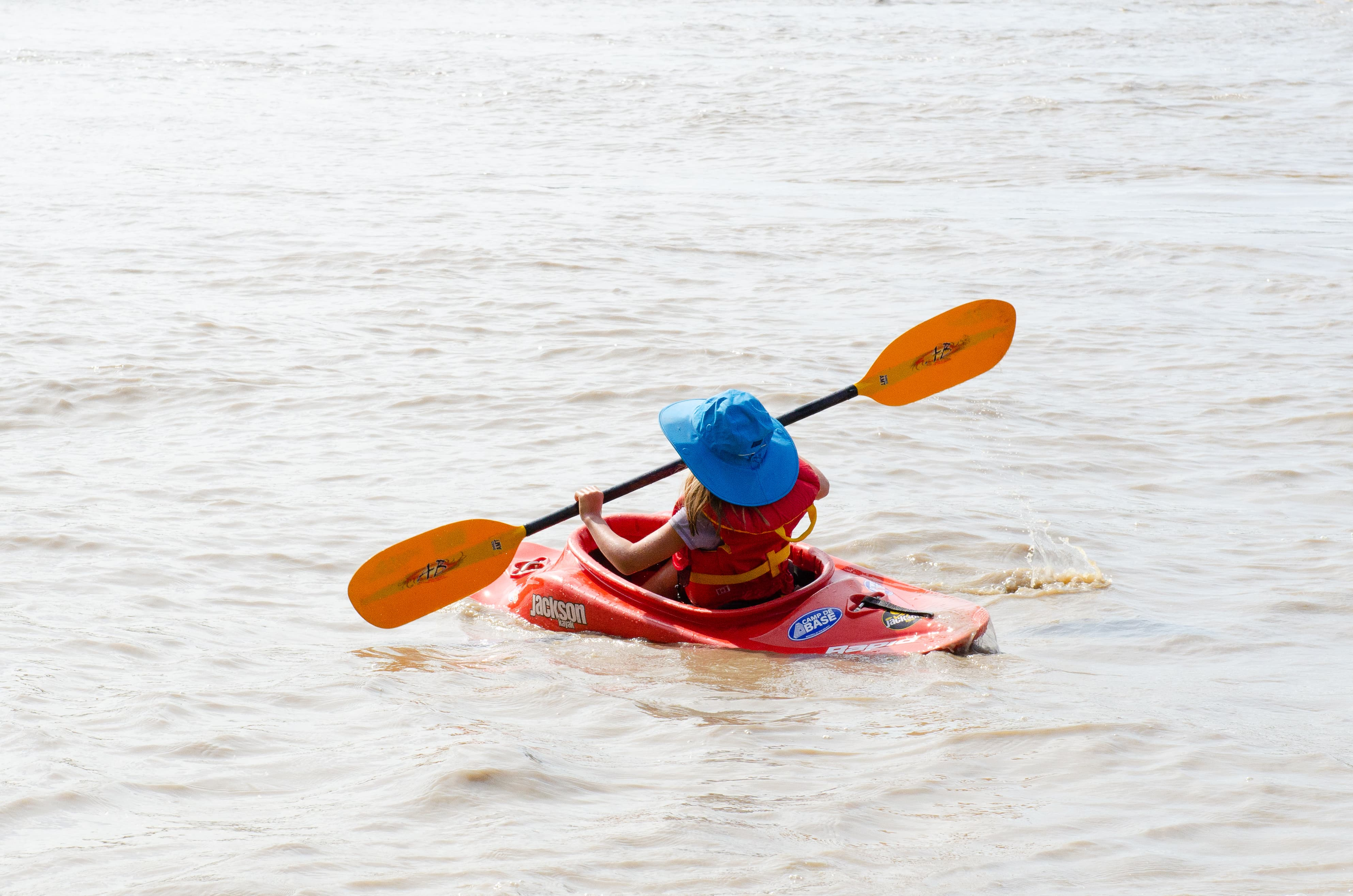 A little kid paddles on a river.
